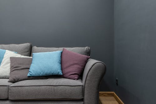 Part of soft modern gray sofa with armrest and abundance of bright pillows placed near wall in light room at home