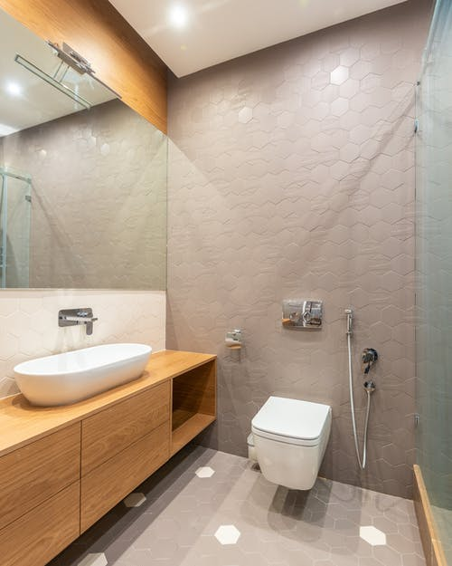 Wooden cabinet with sink with faucet at wall with mirror placed near modern bidet in contemporary spacious bathroom at home