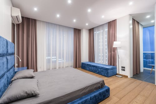 Comfortable blue bed with gray bedclothes placed in contemporary spacious bedroom with curtains on windows and lamp near pouf at home