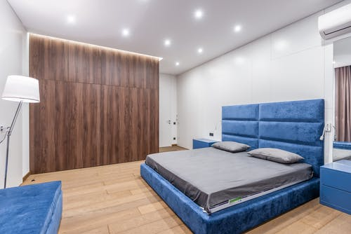 Comfortable blue bed with gray bedclothes placed between bedside tables in modern light spacious bedroom with wooden wardrobe at home