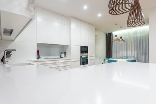 Empty kitchen counter against white cupboards and modern appliances near chairs at table placed near window in spacious stylish apartment