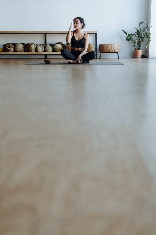 A Woman Sitting on a Yoga Mat