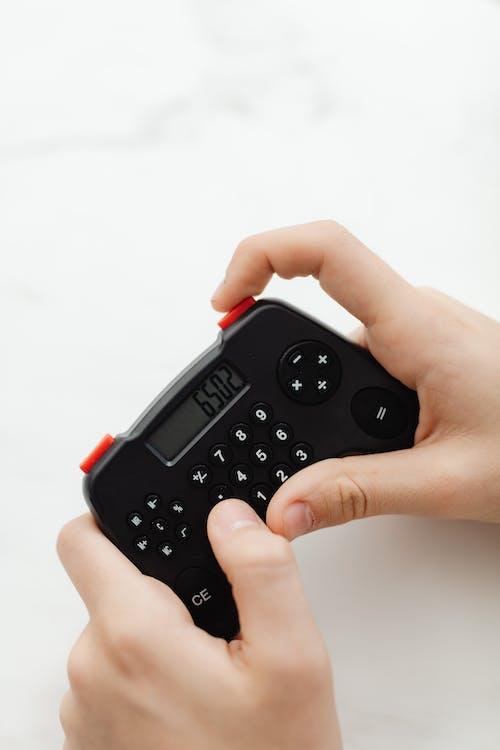 Person Holding A Black Portable Controller