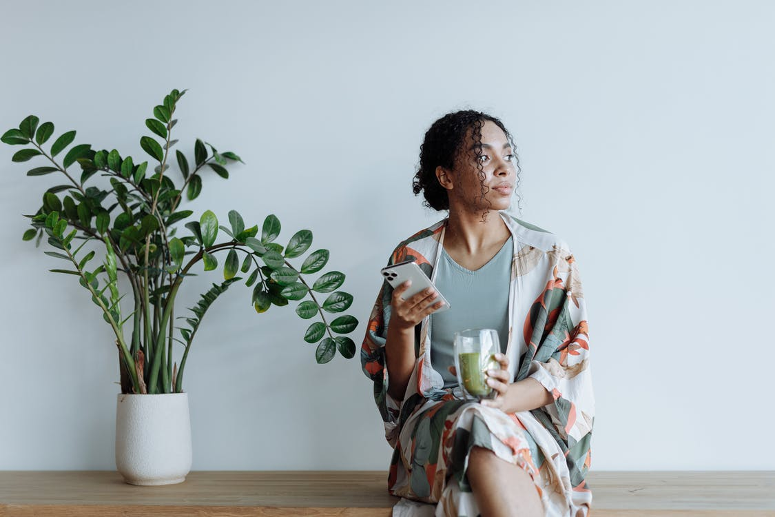 Photo of Woman Sitting Beside an Indoor Plant