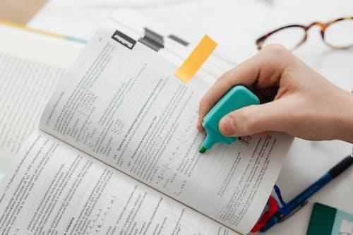 Person Using A Blue Highlighter Pen