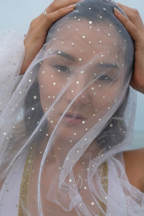 Serious young ethnic lady in white veil with necklace looking at camera with hands on head under sky in daytime