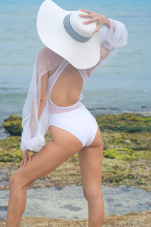 Back view of anonymous slim female in white trendy swimsuit with sleeves and hat standing on shore near sea in summer day