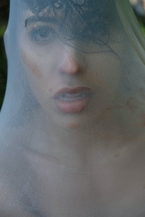 Confident adult lady with white wet cloth on face and makeup looking at camera with open mouth in light place