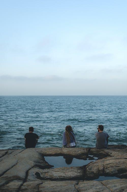 2 Person Sitting on Rock Near Sea