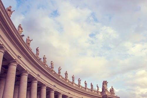 Edificio De Hormigón Gris Con Estatuas Humanas Bajo Un Cielo Nublado