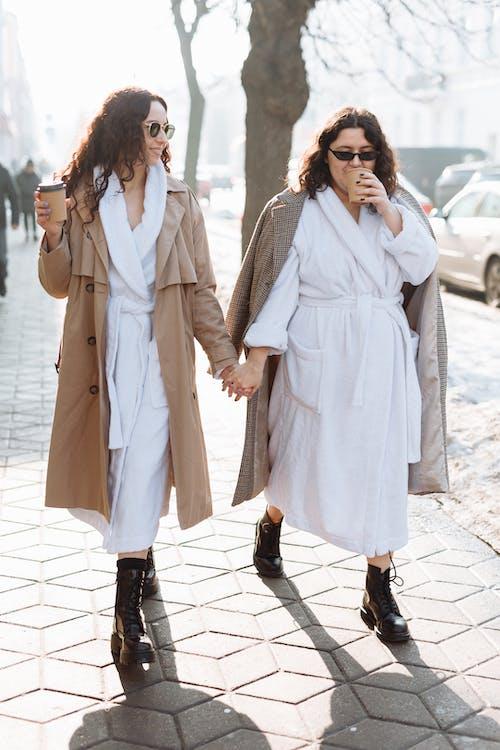 Women in White Bathrobe Holding Hands While Walking