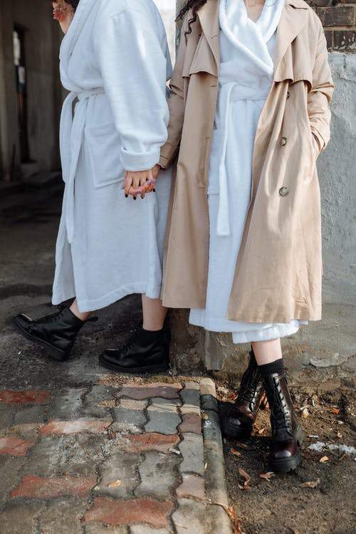 Person in White Bathrobe Holding Hands with Person in Brown Coat