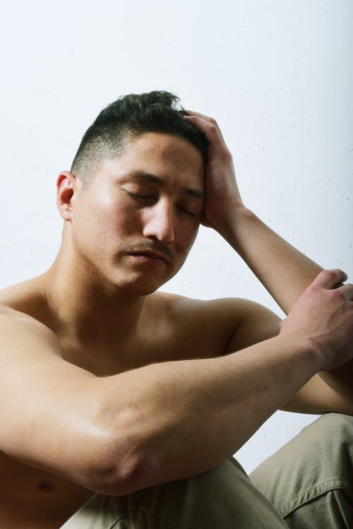 Depressed man touching head on light background