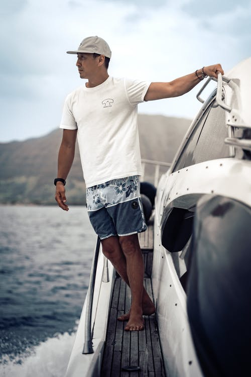 Full body ethnic male in summer wear standing on modern yacht floating on rippling sea in hilly sunny nature