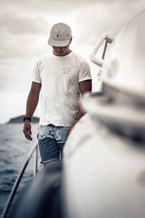 Contemplative ethnic man standing on yacht floating on sea