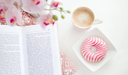 A book, cup of coffee and flavoured donut on Square White Ceramic Bowl