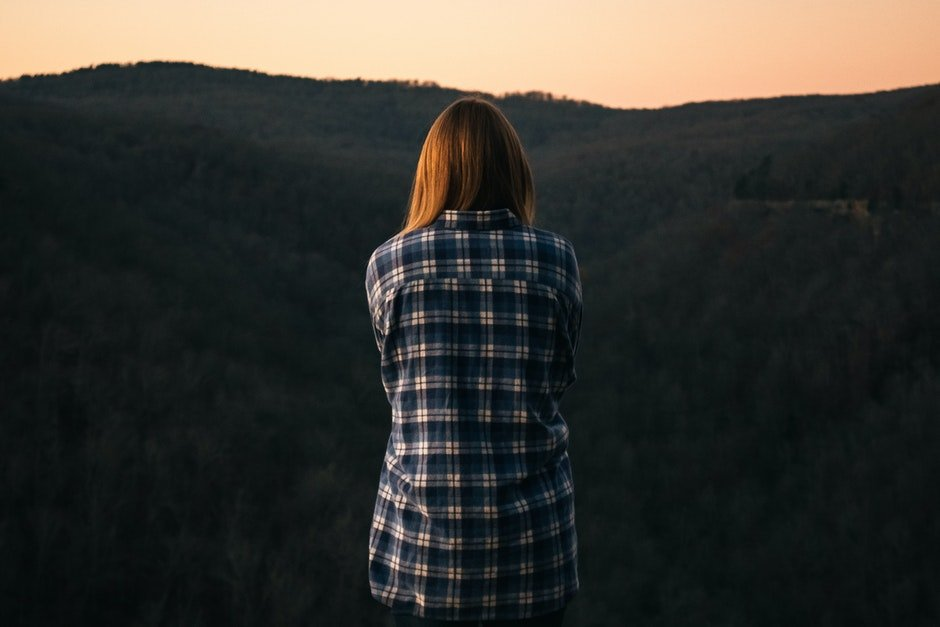 Woman Wearing Blue and White Plaid Dress Shirt in Front of Green Mountain