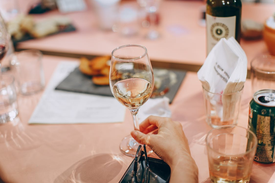 Person Holding Wine Glass Near Clear Shot Glasses
