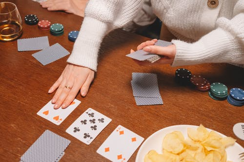 Person in White Long Sleeve Shirt Holding Playing Cards