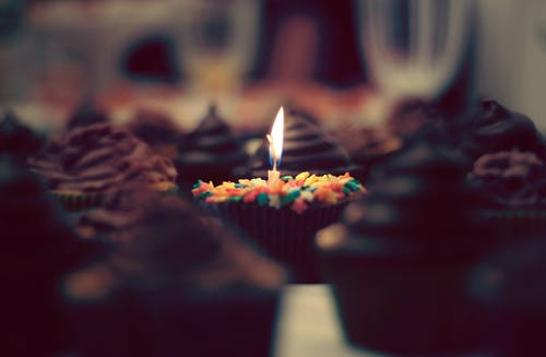 Burning candle with cupcake on table