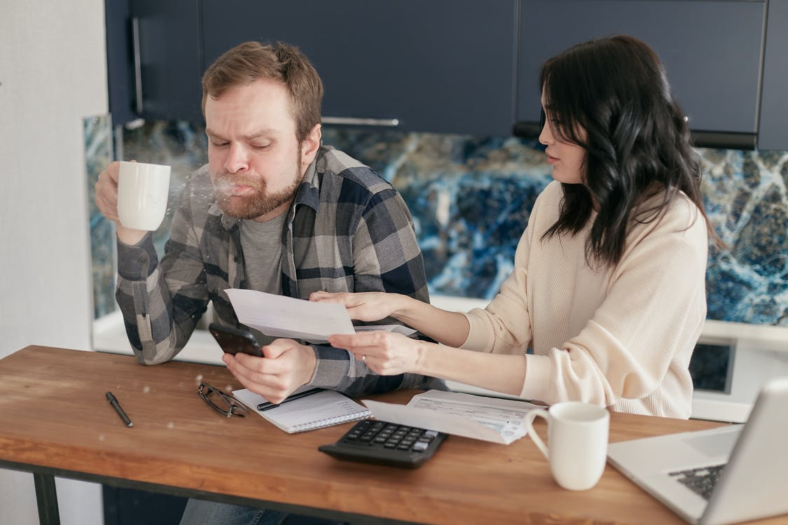 image of couple looking over utility bills, running toilet high water cost
