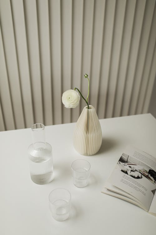 White Ceramic Vase Beside Clear Drinking Glass on White Table