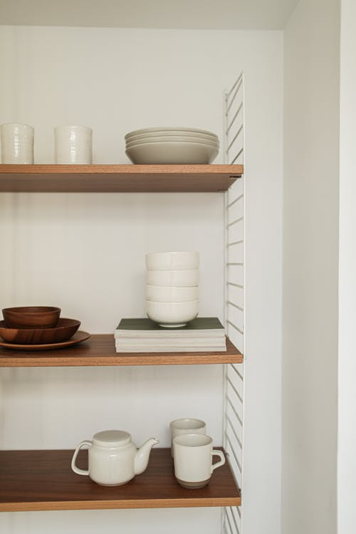 White Ceramic Teacup on Brown Wooden Shelf