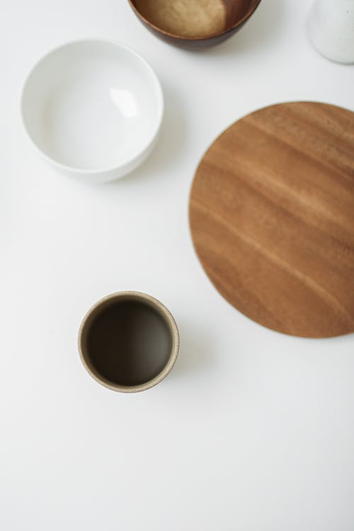 White Ceramic Cup Beside Brown Wooden Round Coaster