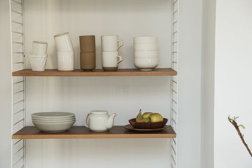 White Ceramic Mugs on Brown Wooden Rack