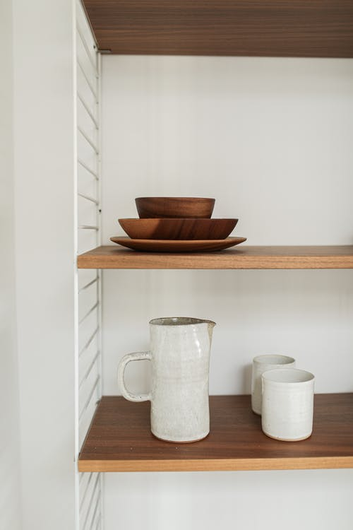 White Ceramic Pitcher on Brown Wooden Shelf