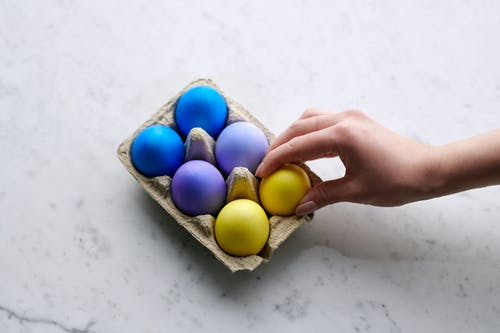 Person Holding Yellow Egg With Blue Egg