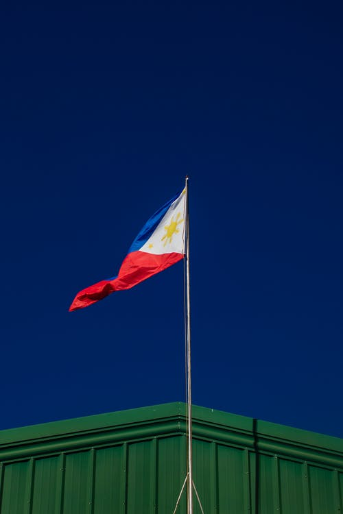 From below of national flag of Philippines placed on flagpole against cloudless blue sky