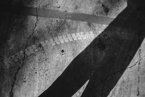 Black and white of linear shadow on cracked concrete wall with traces of dye