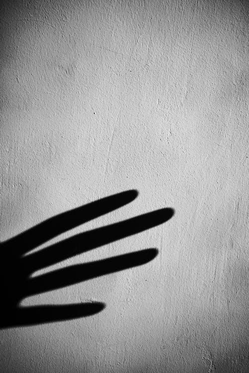 Shadow of crop hand on gray wall