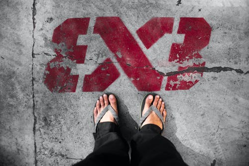 Crop anonymous person in slippers standing on cracked asphalt near shabby red graffiti