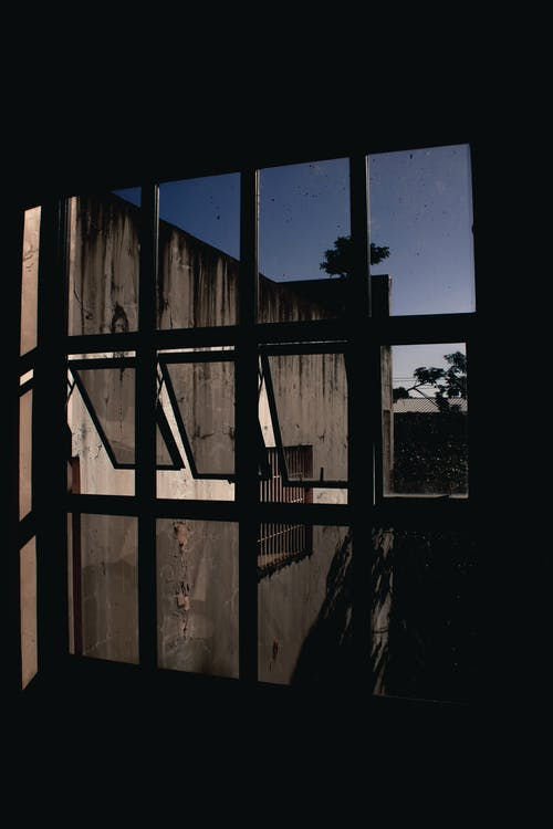 Abandoned gray building with shabby walls through window of dark room in evening