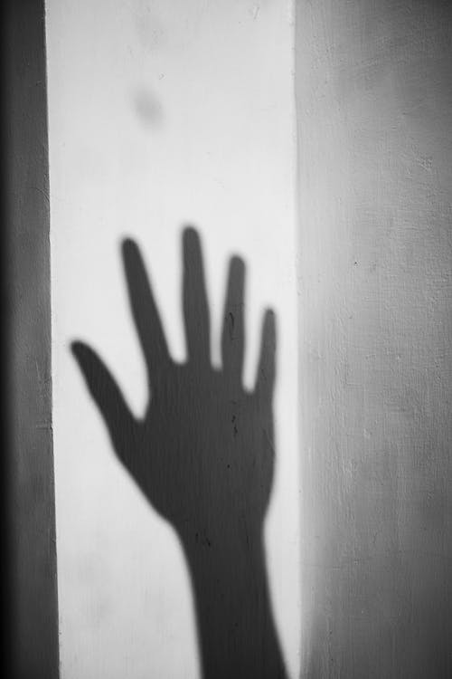 Shadow of hand on white wall