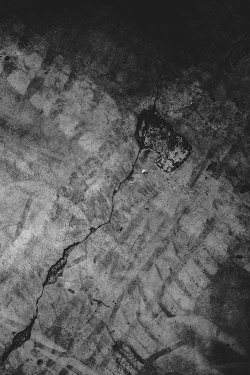 Rough concrete surface with crack and hole