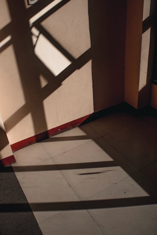 High angle of part of empty residential building with shadows on wall and tiled floor in sunlight