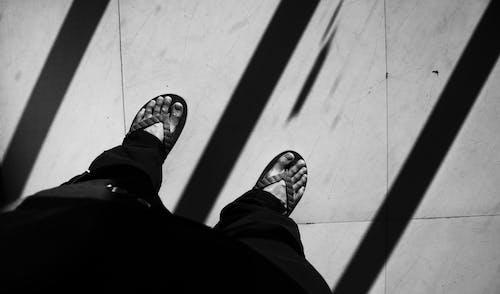 Man in summer slippers standing on tiled floor