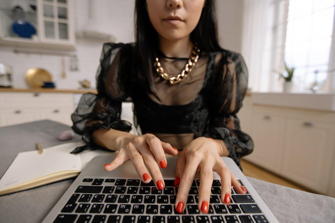 Woman in Black Long Sleeve Shirt Using Macbook Pro