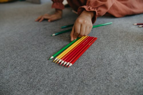 Close-Up Shot of a Person Holding a Colored Pencil