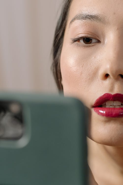Half Face Shot Of Woman With Red Lipstick Looking At Her Phone