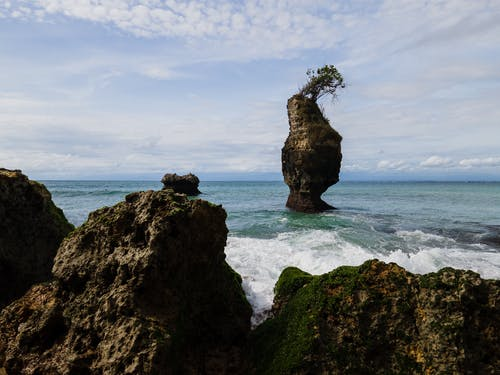 Brown Rock Formation on Sea Under White Clouds and Blue Sky