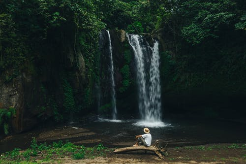 Man in White Shirt and Brown Shorts Sitting on Brown Wooden Chair in Front of Waterfalls
