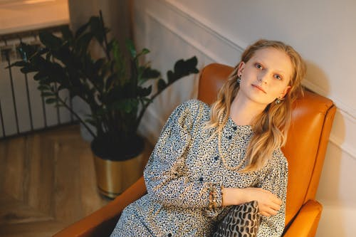 Woman Sitting on a Brown Armchair while Looking at the Camera