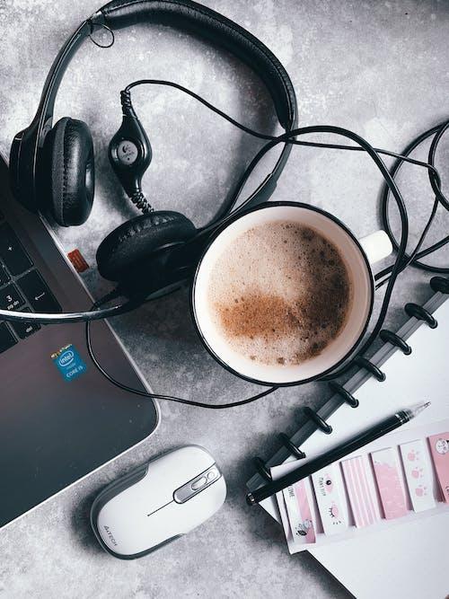 Black Corded Headphones Beside White Ceramic Mug