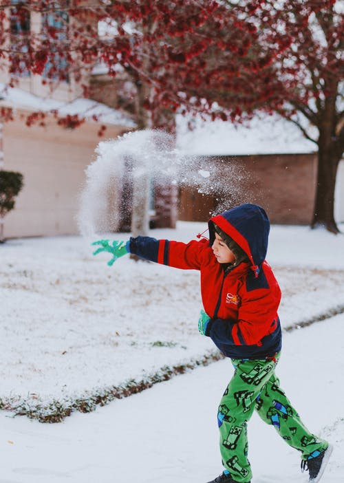 Boy in Red and Black Jacket and Green Pants Standing on Snow Covered Ground