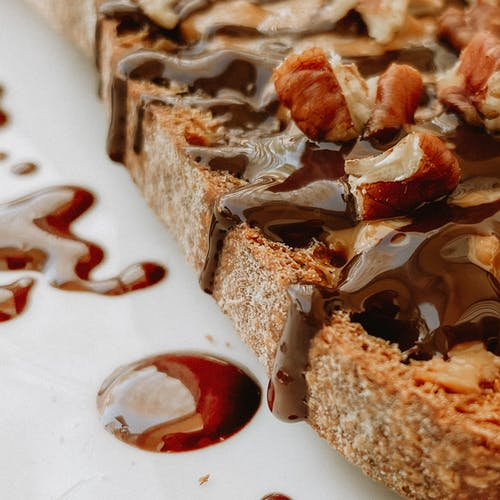 Brown Bread With Chocolate Syrup on White Ceramic Plate