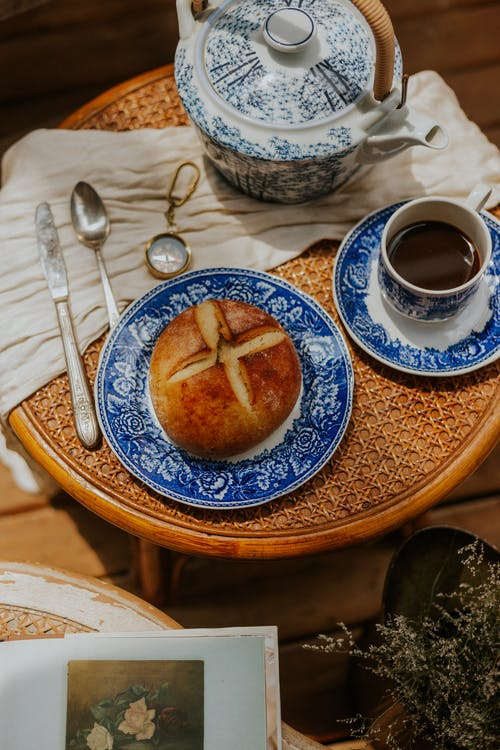 White and Blue Ceramic Teacup on Brown Ceramic Saucer Beside Stainless Steel Spoon and Fork